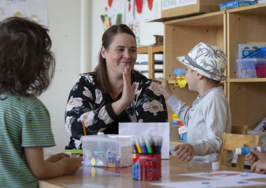 Förskolepersonal och barn gör high five