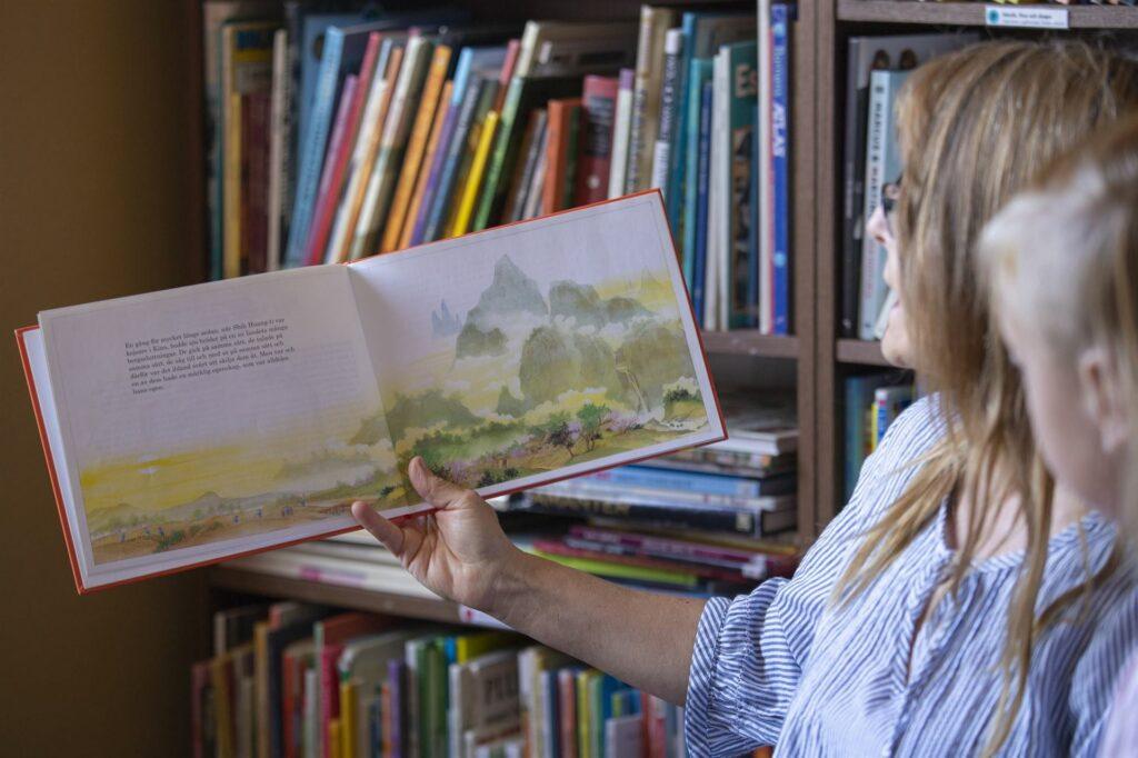 Anna läser en barnbok i biblioteket