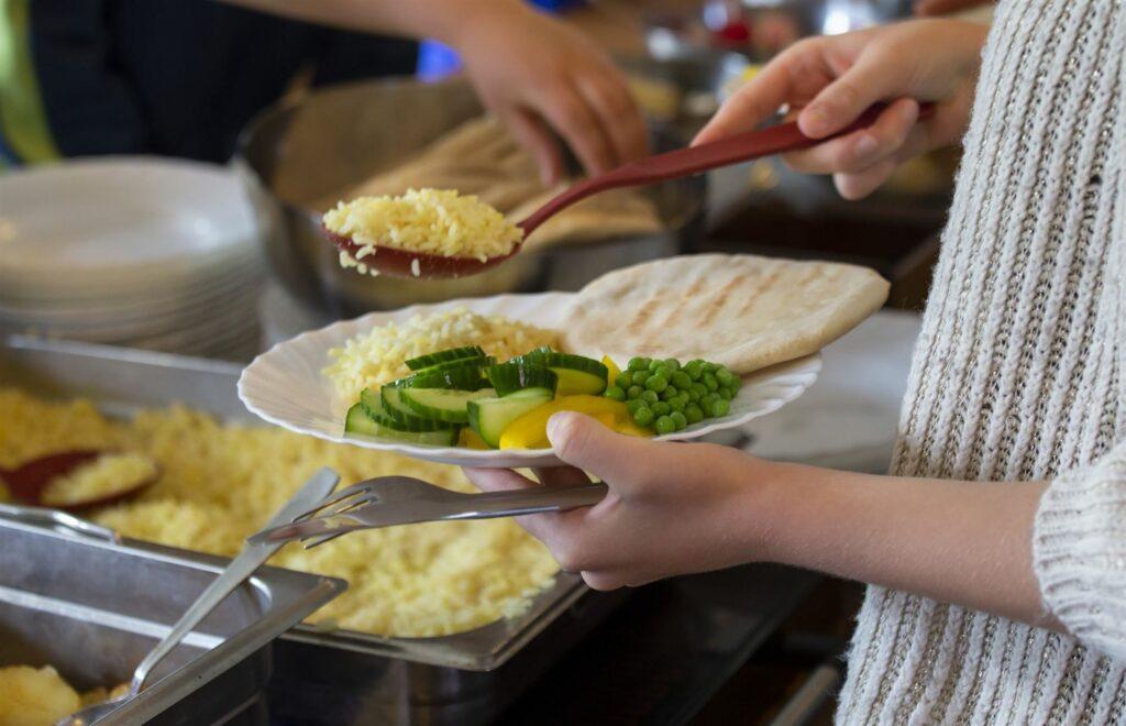 Barn lägger upp mat på tallrik i skolrestaurangen